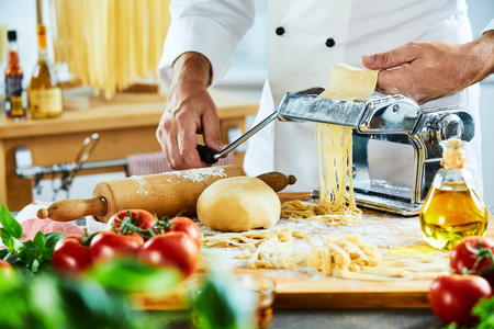 Adult male chef making noodles on top of cutting board next to other vegetables with large kitchen in background