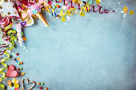 Kleurrijke eenhoorn carnaval grens over een koele blauwe gestructureerde achtergrond met kopie ruimte met feestmutsen, snoep, slingers en harten