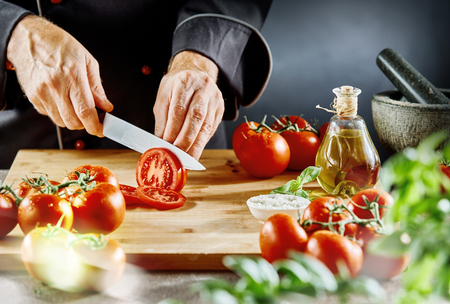 Man wearing cook suit cutting ripe tomatoes into thin slices sitting on cutting board next to mortar and pestle