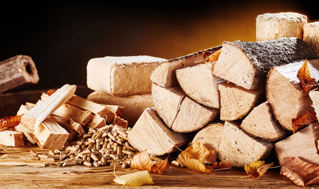 Assorted forms of natural wood heating for autumn or fall with stacked logs, pellets and rectangular blocks of compressed sawdust and chopped kindling for a hot fire