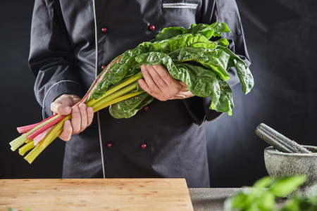 Chef holding a bunch of fresh healthy raw Swiss chard in his kitchen with chopping board, herbs and pestle and mortar in a close up cropped view