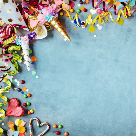 Carnival border with colorful party hats, candy and streamers on a texture blue background with copy space in square format Stock Photo