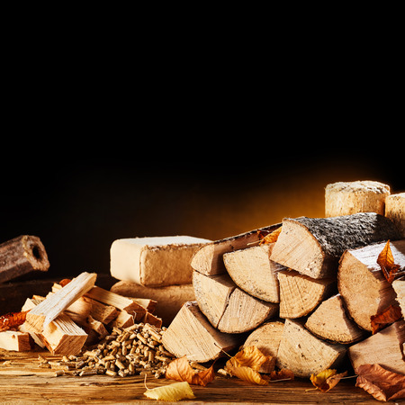 Dried logs, pellets and blocks of compressed sawdust in an autumn still life conceptual of natural biofuels for heating in square format with copy space