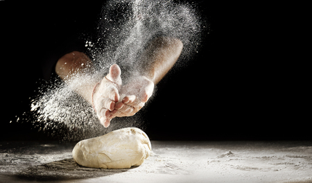Pastry chef clapping his hands to dust a mound of freshly prepared pastry with flour in a freeze motion of a cloud of flour midair on black with copy space