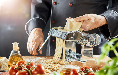 Man grinding brown dough into stringy noodles on top of cutting board near bottle of olive oil and tomatoes Zdjęcie Seryjne
