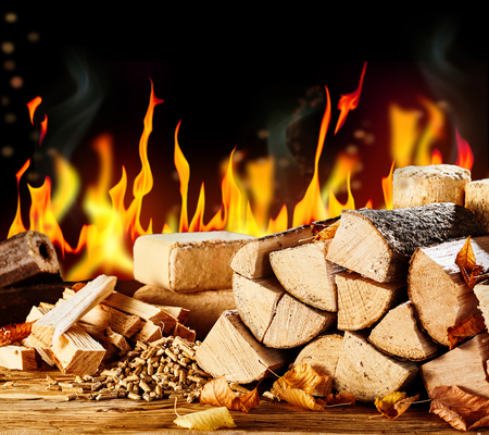 Multiple chopped wood logs and small wooden scraps sitting in front of bright orange flaming background