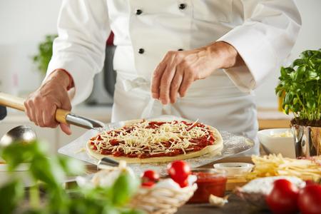 Der Küchenchef streut Mozzarella-Käse auf einem Paddel auf eine rohe Pizzabasis, während er ein traditionelles mediterranes Essen zubereitet, ganz nah an seinen Händen