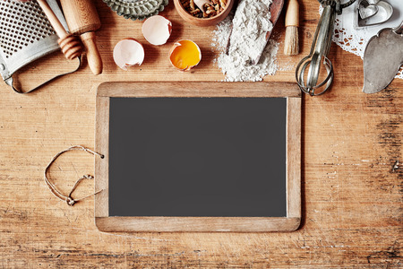 Baking border with an assortment of vintage cookware, egg and flour above a blank school slate with copy space for your recipe or menu