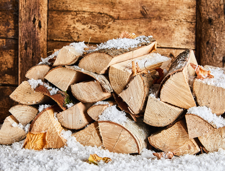 Winter woodpile outside a rustic wooden house covered in a fresh coating of snow and colorful autumn leaves
