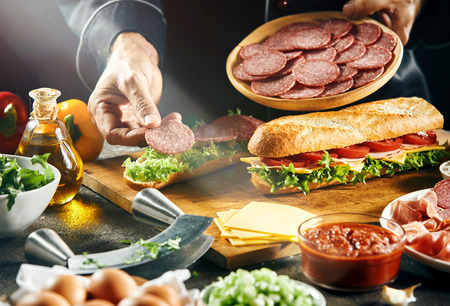 Chef preparing tasty fresh baguette sandwiches with cheese, tomato, spicy salami, ham and lettuce in a close up on his hands Stock Photo