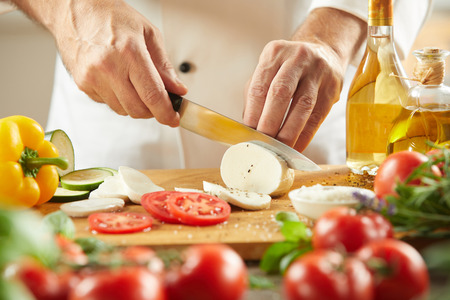Chef preparing fresh mozzarella with tomatoes on wooden cutting board