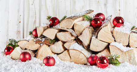 Winter stockpile of wood logs in snow at Xmas decorated with colorful red baubles and pine foliage against a white wooden rustic wall Imagens - 109907780
