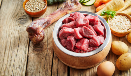 Healthy fresh pet food ingredients on a rustic floor including raw meat in a bowl, a large bone, vegetables , eggs and grains