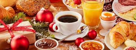 Tasty fresh Christmas Intercontinental breakfast in a colorful panorama banner with coffee, orange juice, assorted fresh food, gifts and decorations