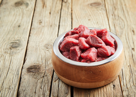 Fresh raw diced meat in a stylish wood and metal dog bowl on an old wooden floor with cracked floorboards and copy space