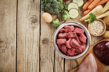 Fresh ingredients for a healthy nutritious dog diet with a bowl of chopped raw beef, chicken, liver, egg. assorted vegetables and grains in an overhead view on wood with copy space