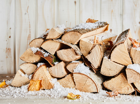 Small woodpile of dried logs in winter snow with scattered autumn leaves against a rustic white painted wooden wall