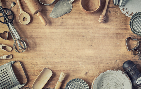 Selection of old vintage cookware forming a border on rustic natural wood with central copy space in a flat lay still life