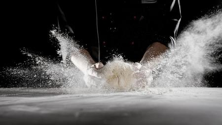 Trabajador de restaurante golpeando la masa sobre la mesa, lo que hace que la harina blanca en polvo se rocíe en el aire en largas rayas