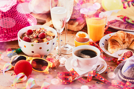 Carnival breakfast with party accessories, streamers and confetti scattered amongst a bowl of cereal, coffee, croissant and fruit juice with two glasses of champagne for celebrating Stock Photo