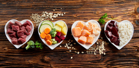 Panorama banner of healthy fresh ingredients for pet food in individual heart-shaped bowls viewed from overhead with chopped raw beef, liver and chicken , mixed vegetables and rains on rustic wood