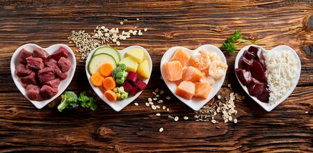 Panoramabanner van gezonde verse ingrediënten voor dierenvoeding in individuele hartvormige kommen, van bovenaf gezien met gehakt rauw rundvlees, lever en kip, gemengde groenten en regen op rustiek hout