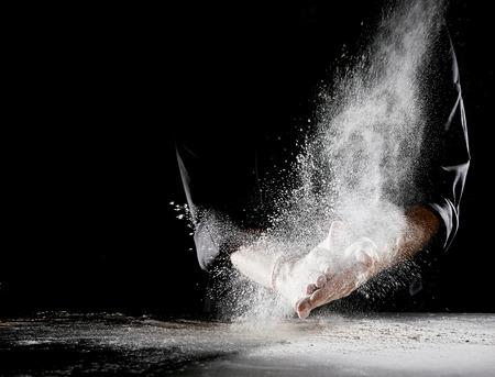 Mehlwolke sprüht in die Luft und verschüttet sich auf flache Tischoberfläche, während Mann, der schwarzes Kochoutfit trägt, Hände reibt