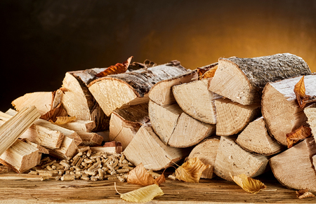 Stack of light colored wood logs sitting on top of brown wooden table in front of orange and black background