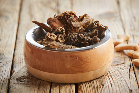 Dog bowl filled with fresh raw chopped tripe or rumen on a rustic wooden floor in a concept of animal nutrition and care