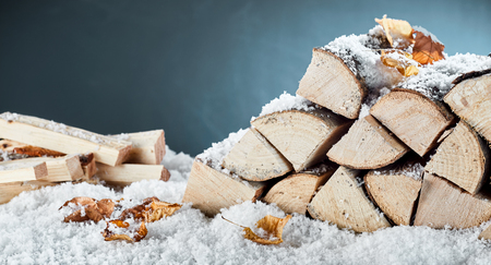 Woodpile with stacked logs and kindling buried in fresh winter snow in a close up view conceptual of natural biofuels for heating Stockfoto