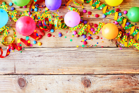 Carnival or birthday background with colorful streamers, confetti and party balloons forming a top border on rustic wood with copy space