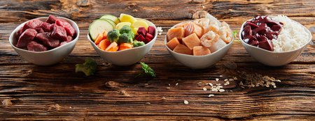 Panorama banner of healthy fresh ingredients for pet food in individual bowls with chopped raw beef, liver and chicken , mixed vegetables and rains on rustic wood