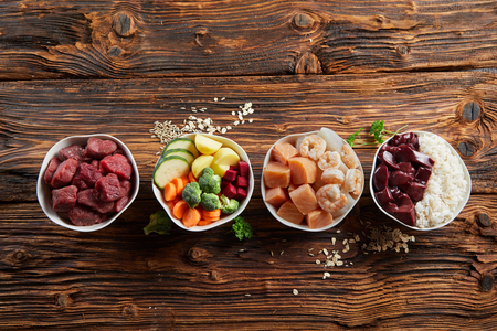 Bowls of fresh ingredients for a healthy animal diet for your dog or cat with raw beef, liver, chicken, vegetables, grains and rice on a rustic wood background with copy space