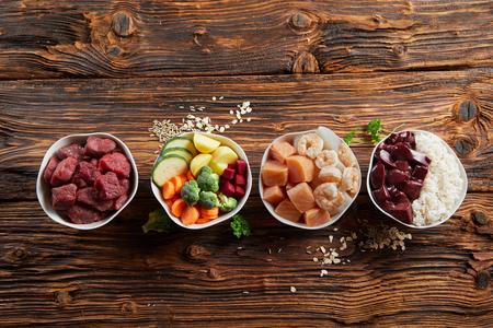 Kommen met verse ingrediënten voor een gezond dierlijk dieet voor uw hond of kat met rauw rundvlees, lever, kip, groenten, granen en rijst op een rustieke houten achtergrond met kopie ruimte Stockfoto