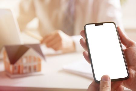Hands holding a mobile phone with blank display for copy space while planning the construction of a house in the office of an architect or a real estate agent