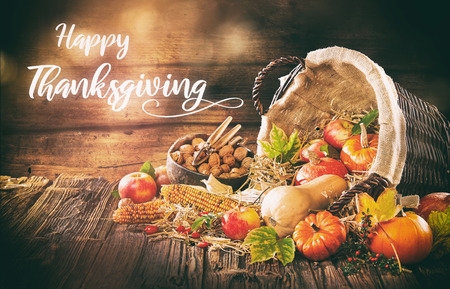 Handgeschriebene Thanksgiving-Einladung mit einem Korb voller frischer Ernte wie Apfelmais und Kürbisse für Halloween