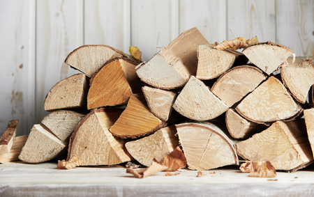 Stacked woodpile of dried wooden logs ready for heating the house or a barbecue in autumn in a close up view outdoors