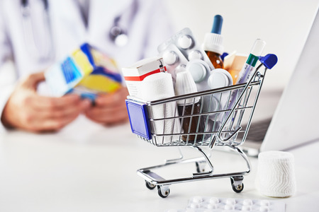 Mini shopping cart full of medicines in pharmacy against pharmacist