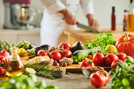 Cutting board completely covered with assorted food and man in chef outfit chopping herbs in background