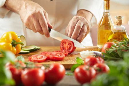 Chef slicing fresh tomatoes for a salad in a low angle view of the knife and chopping board over assorted fresh vegetable ingredients 스톡 콘텐츠