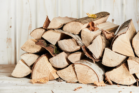 Woodpile of chopped and split firewood with autumn leaves in front of an old white painted wall outdoors Stockfoto - 109220209