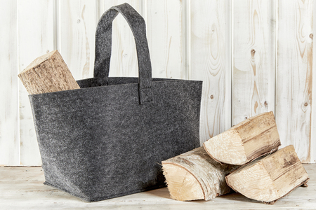 Rustic textile bag with chopped firewood for a barbecue or winter heating in front of a white painted wooden wall with copy space Foto de archivo - 109220232