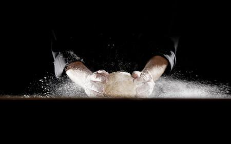 Homme non identifié en tenue noire à l'aide de ses mains claquant la pâte dans la table, faisant voler la farine dans les airs Banque d'images