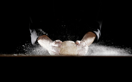 Unidentified man in black outfit using his hands slamming dough into table causing flour to fly into the air