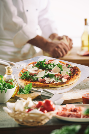 Chef preparing a pizza with fresh herbs and flaked parmesan cheese with out of focus ingredients in the foreground and a view to his hands