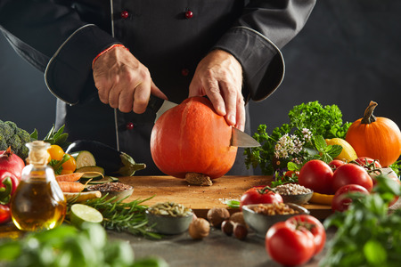 Restaurant worker in black suit cutting open small orange pumpkin sitting on wooden cutting board surrounded by vegetables