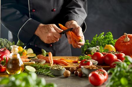 Uomo vestito da chef nero che sbuccia una carota su un tagliere di legno seduto sopra un tavolo scuro e un'oscurità nebbiosa sullo sfondo