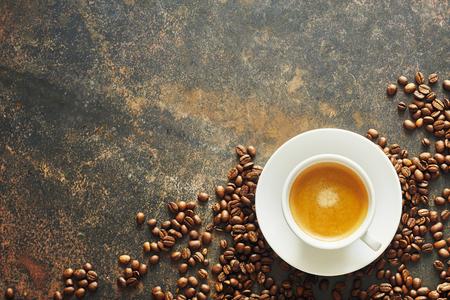 Taza de café con leche en una taza y platillo de cerámica blanca genérica rodeada de frijoles tostados en la esquina de una pizarra texturizada con espacio de copia para menú o publicidad