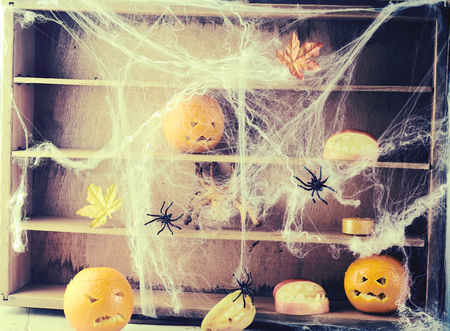 Ghostly Halloween background with spiders and webs covering orange jack-o-lanterns on rustic dilapidated wooden Stock Photo