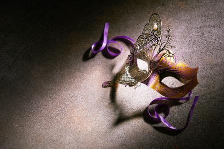 Nahaufnahme einer violetten und braunen Metallmaske, die von hellem Licht beleuchtet wird, das auf einer aufgerauten Oberfläche sitzt